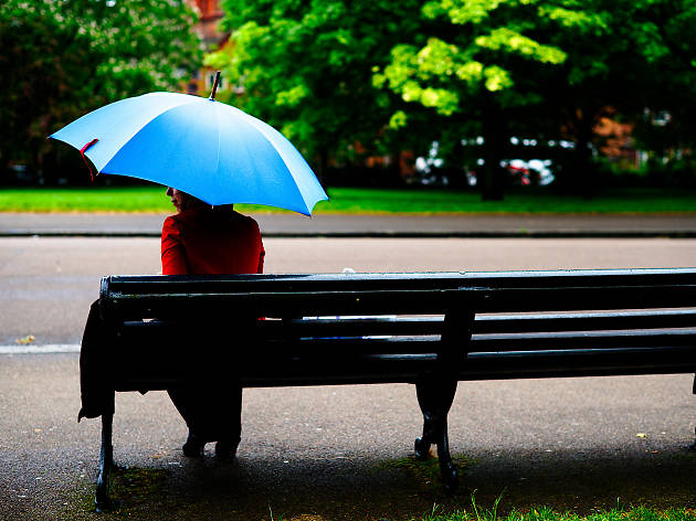 A woman in a red coat with a blue umbrella on a bench.