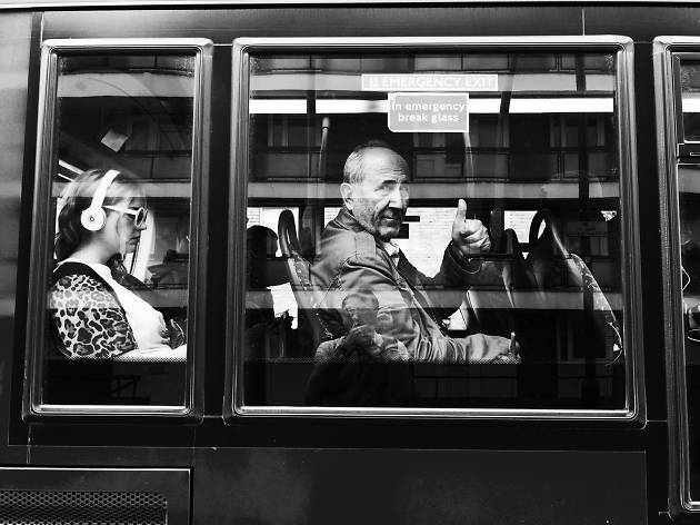 A man gives a thumbs up through the window of a bus.