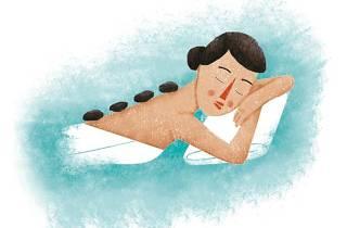 Una mujer recibiendo un masaje de piedras en un spa.