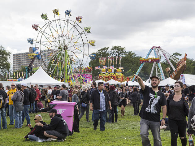 Attendees walk through the midway at day one of Riot Fest.