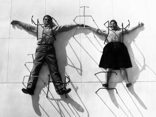 Charles and Ray Eames posing with chair bases. © Eames Office LLC