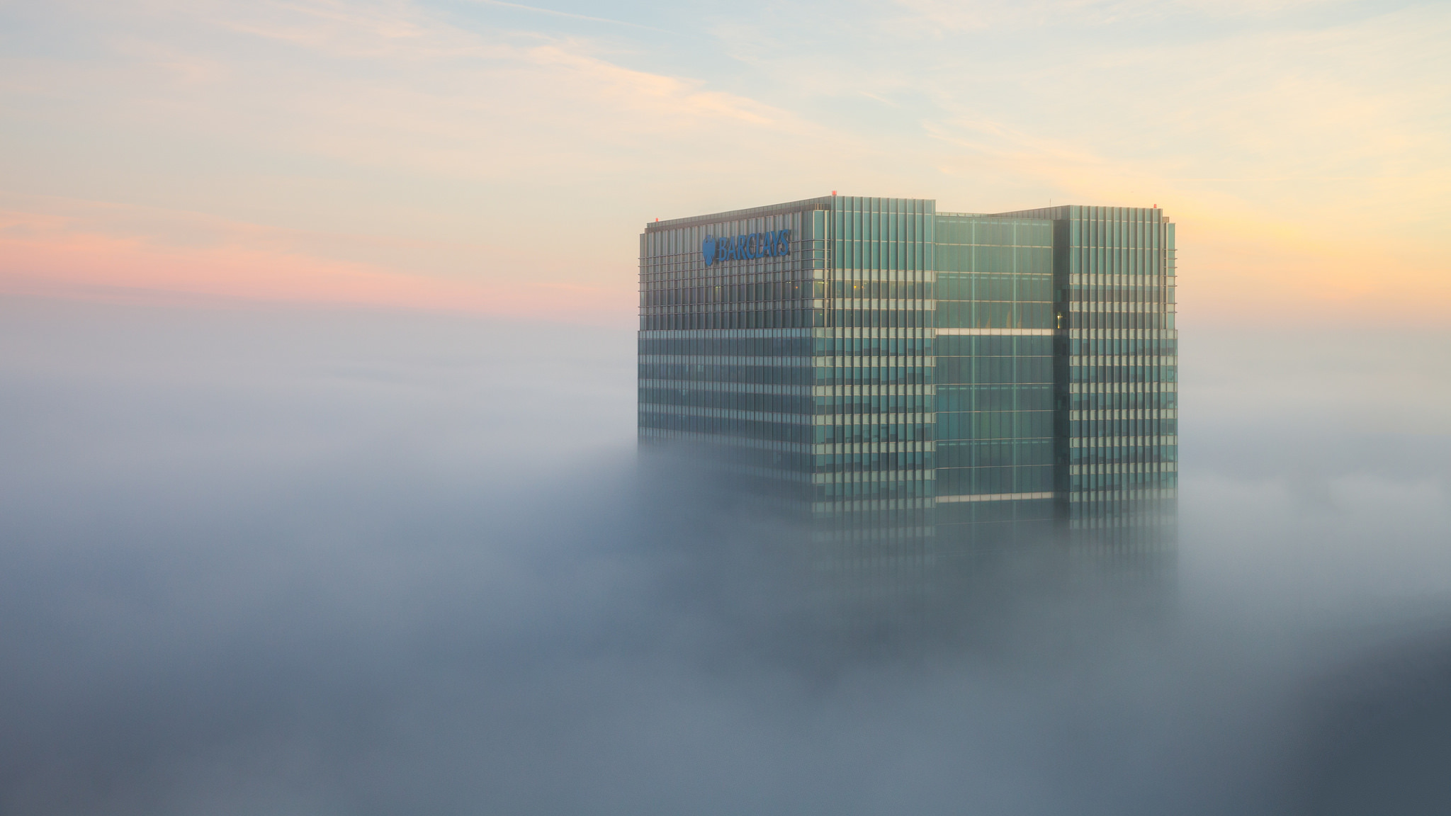 Barclays skyscraper through the fog in London.