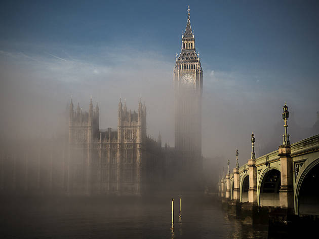 Mist shrouds Big Ben at the Palace of Westminster, as seen over the Thames.