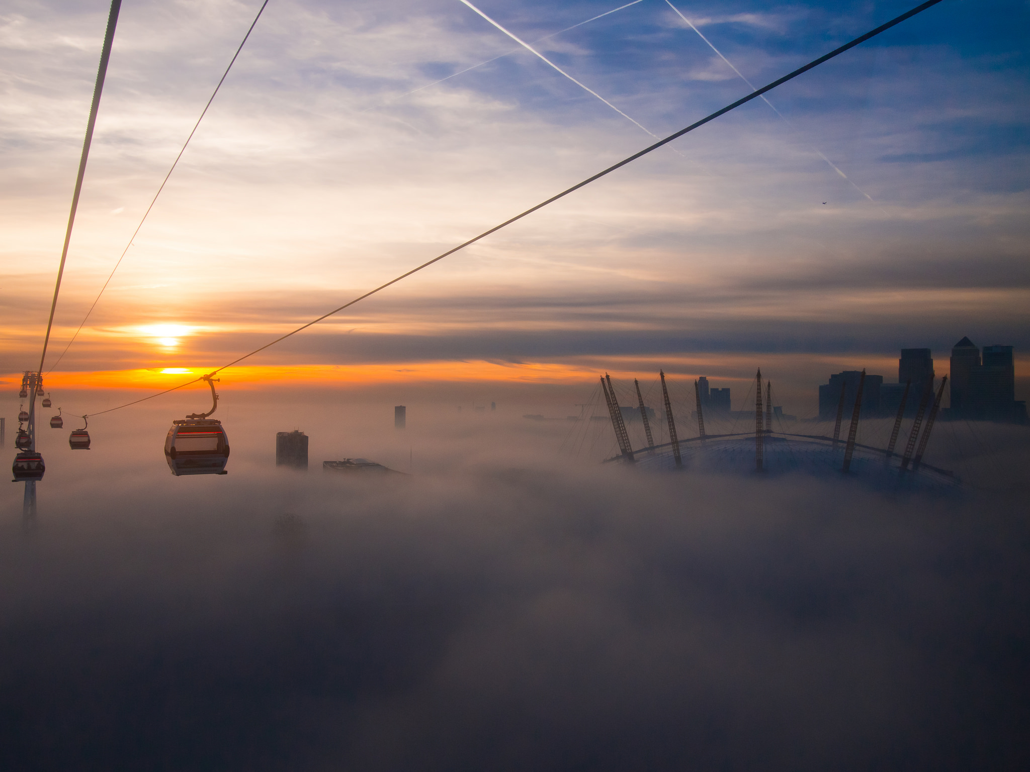 Fog appears to make London's cable car, or the Emirates Air Line, appear to float above the clouds.