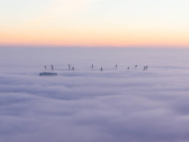 The masts of the O2 Arena, Greenwich, through the fog, in London.