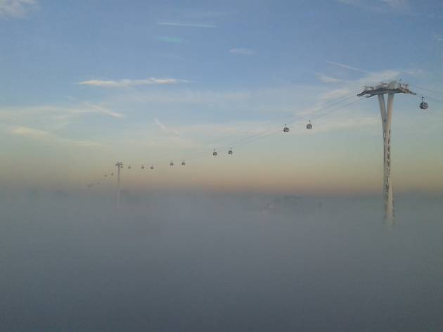The Emirates Air Line cable car above the mist in east London.