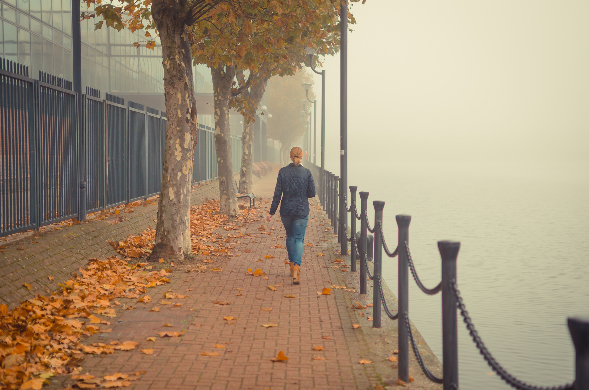 A woman walks by Millwall Outer Dock, London, on a misty day.
