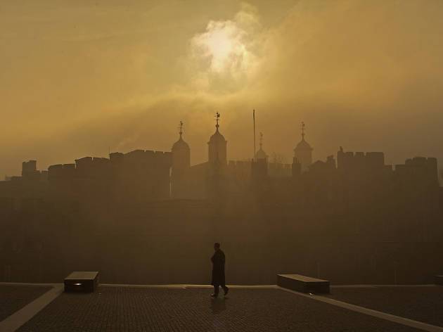 A lone figure patrols the Tower of London's moat during a hazy sunrise.