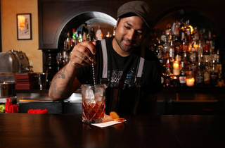 Pasan Wijesena mixing a red cocktail with ice at bar Earl's Juke