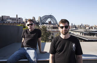 Clayton Knight and Harrison Mills of Odesza sit in front of Harbour Bridge