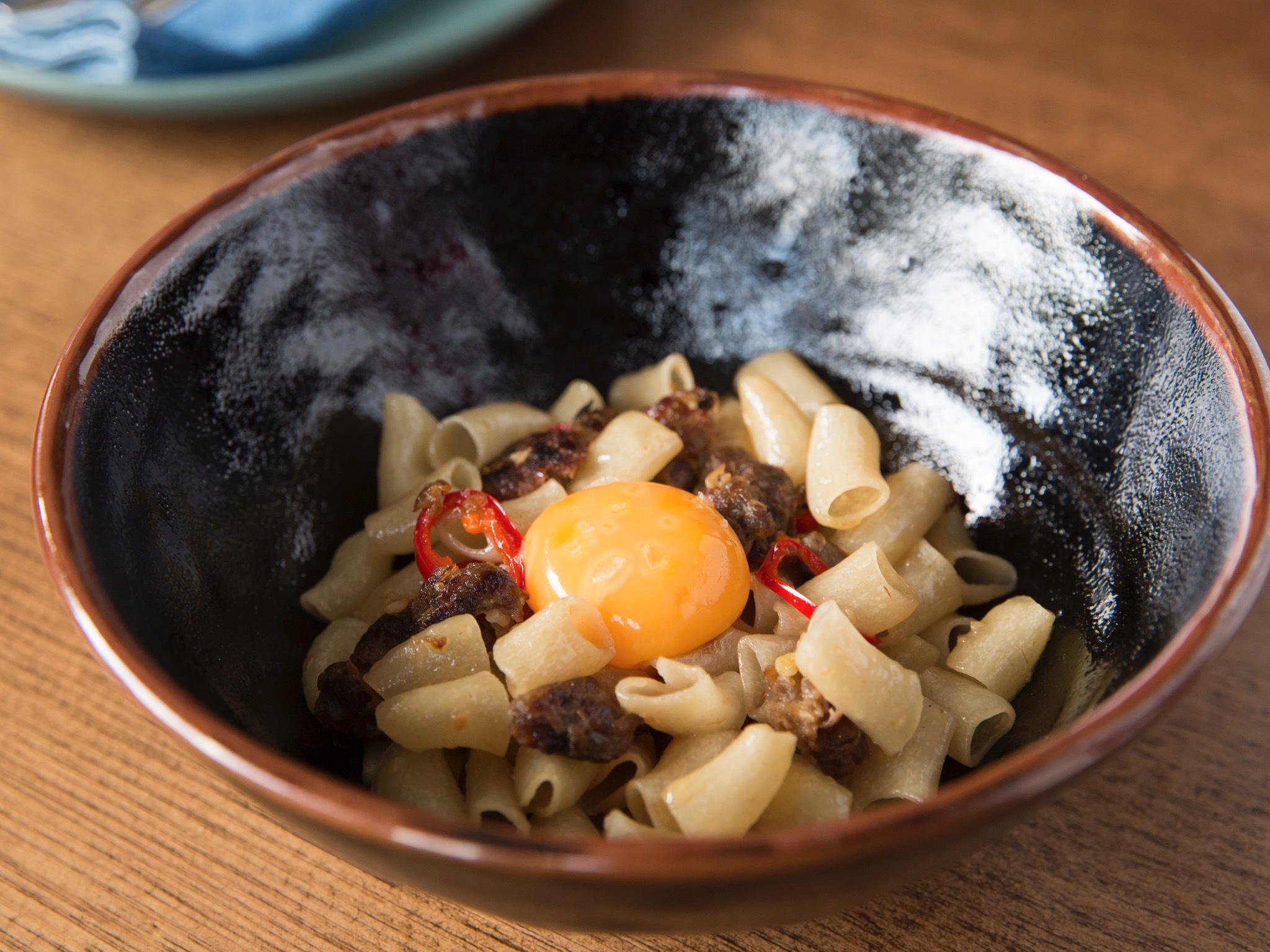 A dish of small tube pasta with slices of chilli and an egg yolk