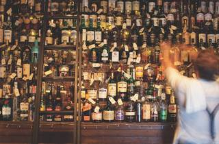 A bartender at Baxter Inn reaching up towards a large wall stack