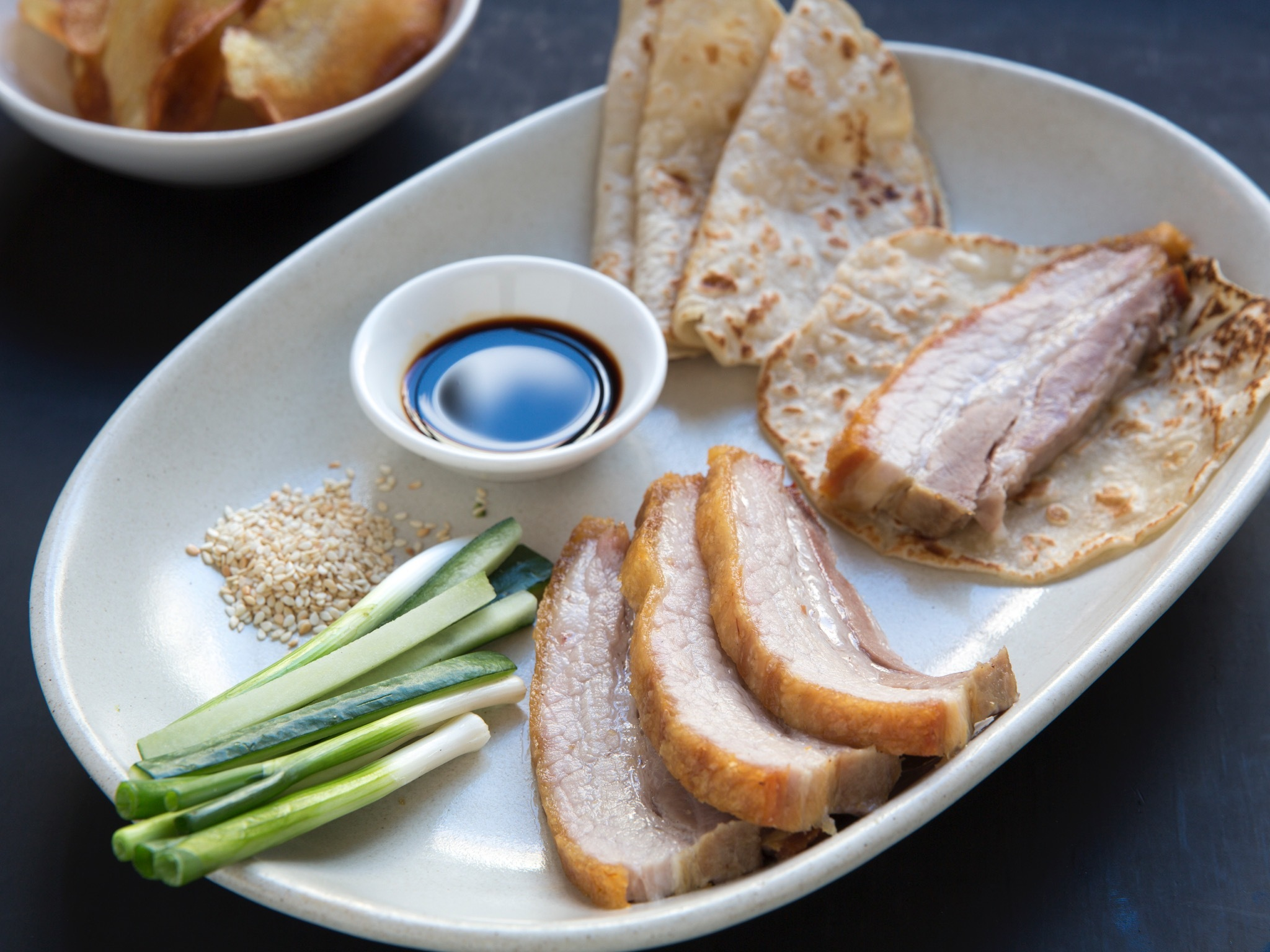 A plate with strips of roast pork, shallots, sesame seeds, dark