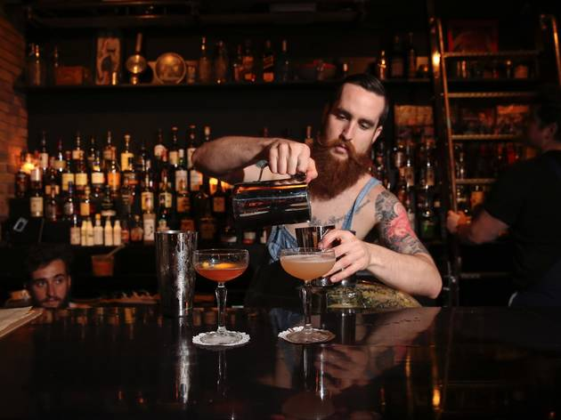 A bartender with a big bear pouring a cocktail into a shaker at