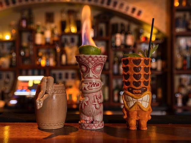 Three cocktails on the bar at Papa Gede's in tiki mugs. The one