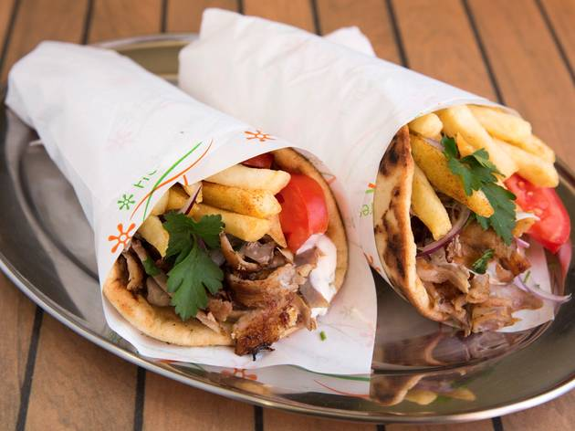Two gyros with meat, chips and tomato wrapped in paper on a meta