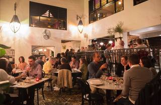 An interior shot of a split level room at Porteno with people si