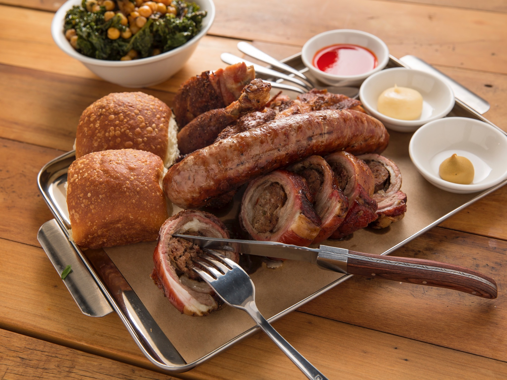 A tray of assorted smoked meats on a metal tray with dipping sau