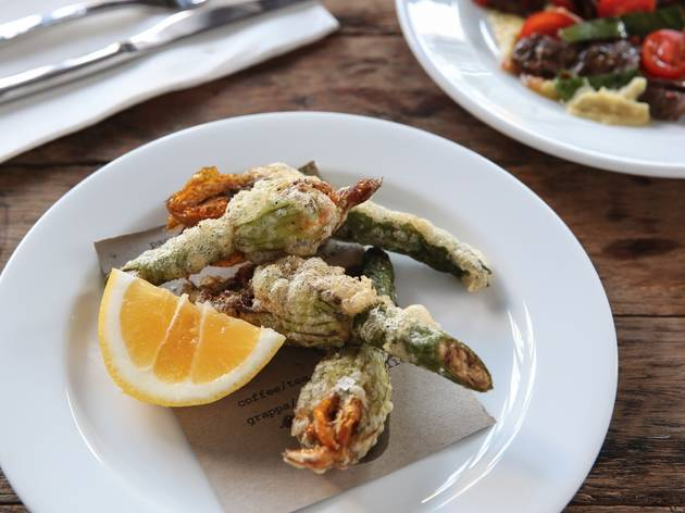 A dish of fried zucchini flowers with a lemon wedge at Sagra