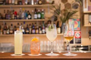 A selection of four different cocktails lined up on the bar at T