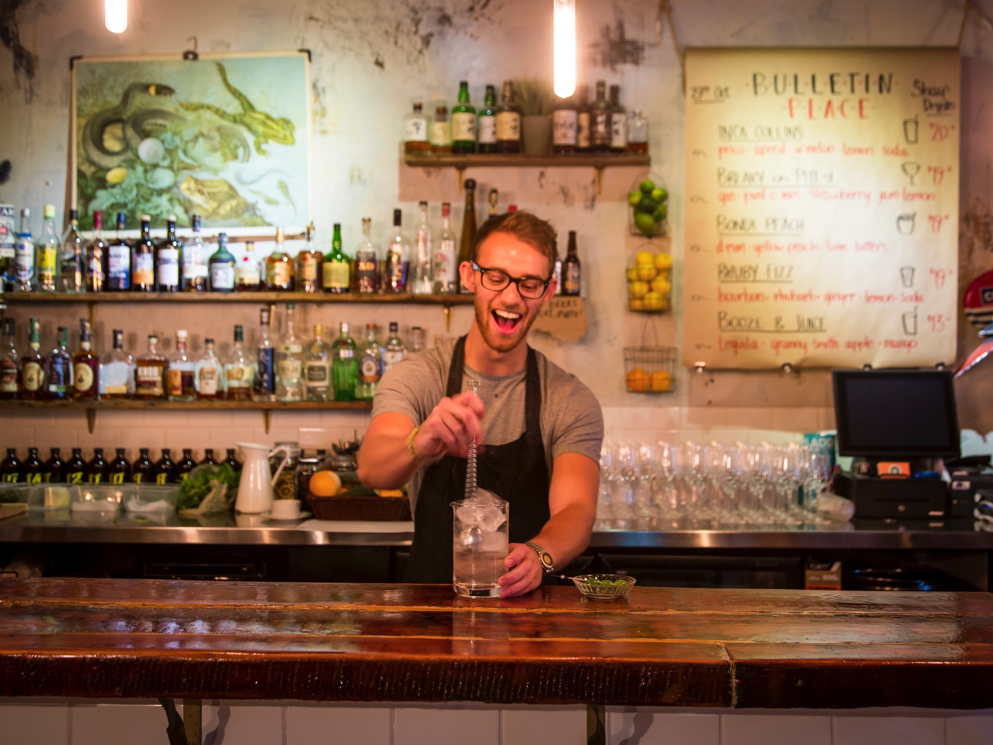A bartender smiling behind the bar at Bulletin Place stiring a c