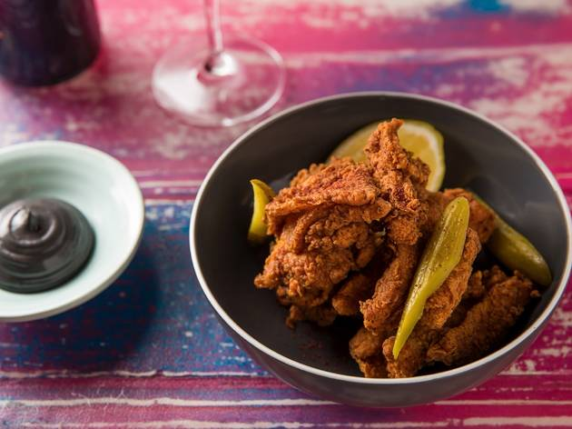 A bowl of fried chicken mixed in with sliced pickles at Thievery