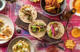 A top down shot of a collection of food dishes on a colourful pr