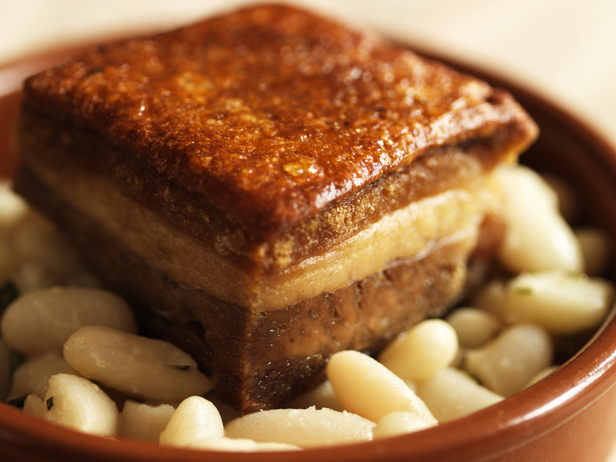 Confit of pork belly with rosemary-scented cannellini beans at Opera Tavern