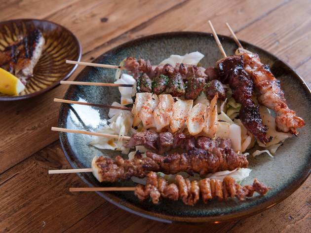 A shot of various grilled meat skewers on a bed of shredded cabb