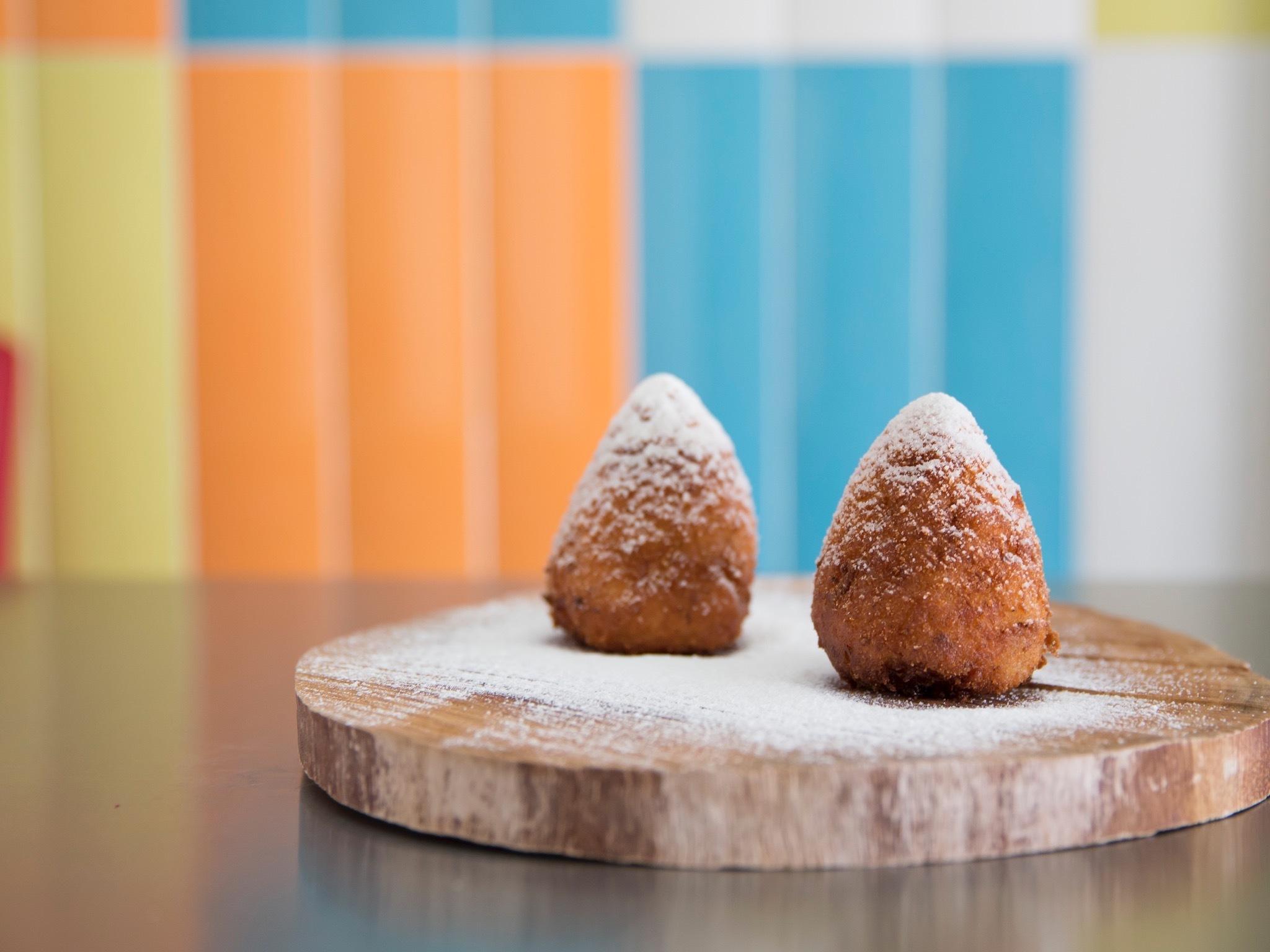 Sweet aranchinis sprinkled sith icing sugar