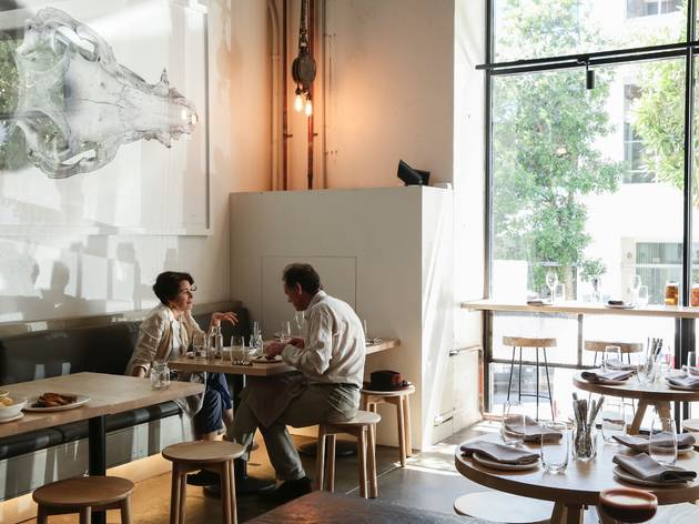 An interior shot at Nomad showing a couple sitting at a table ea