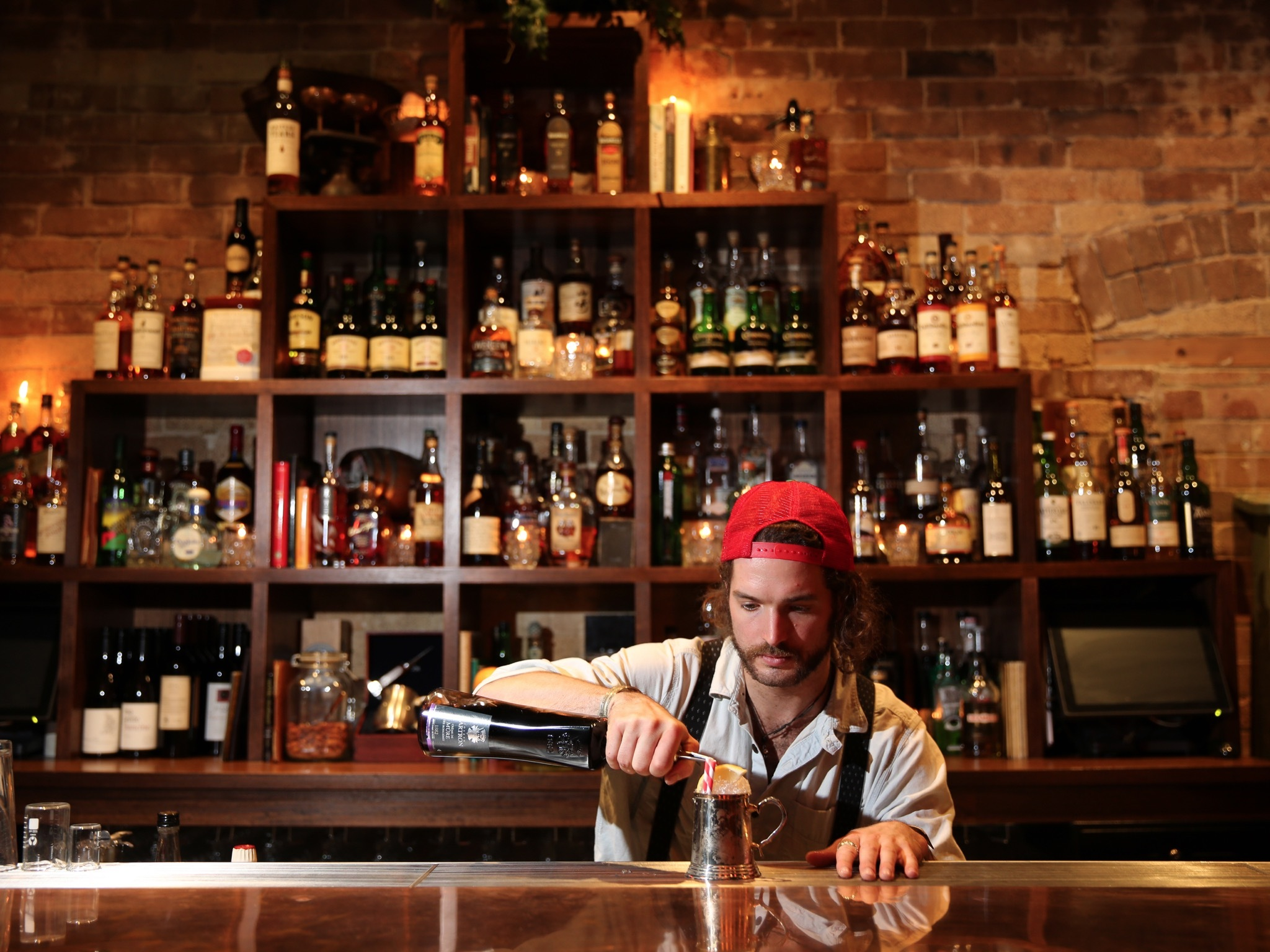 A bartender behind the bar at The Wild Rover wearing a backwards