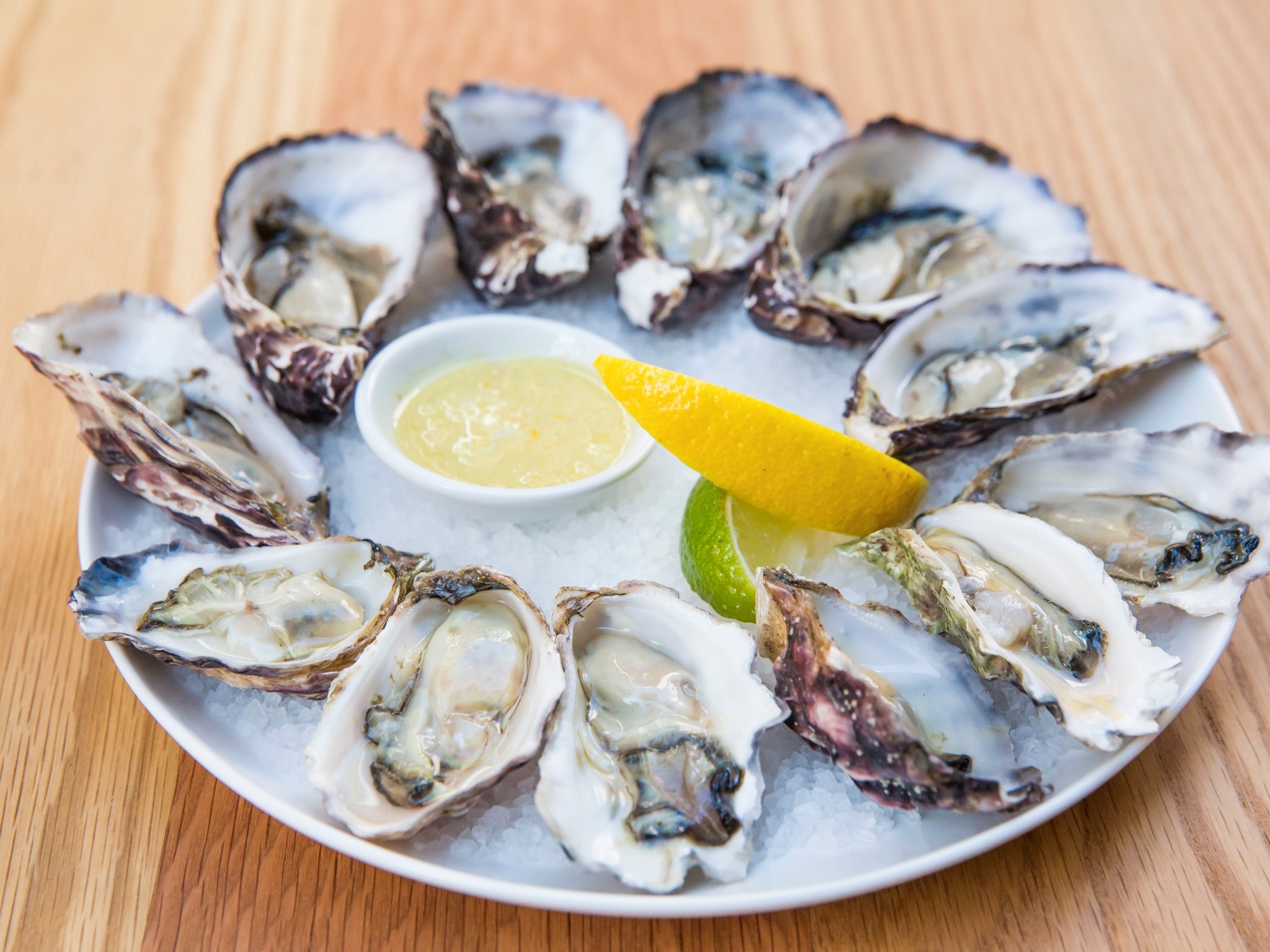 A plate of oysters with a slice of both lemon and lime at Waterm