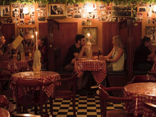 A couple sit at a booth at Frankie's Pizza by the Slice