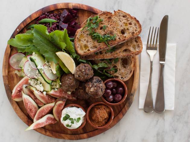 A top down shot of a wooden plate full of bread, lettuce, figs,