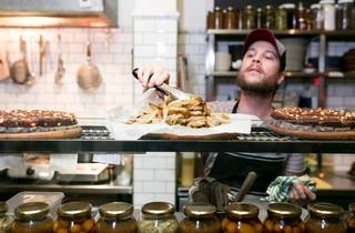 A shot of a chef behind the counter at Cornersmith picking up fo