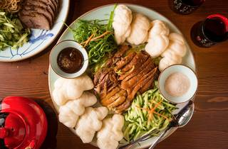 Crispy duck served with vegetables and buns