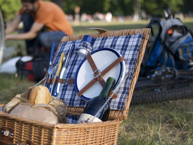 A generic shot of a picnic basket with plates, cutlery, bread an