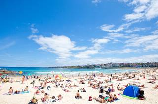 A wide shot of Bondi Beach showing crowds of people both sitting