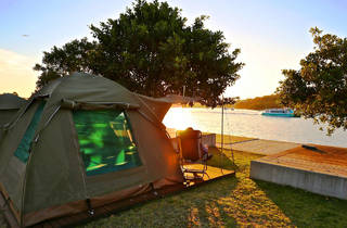 A shot of a tent set up in front of the water as the sunsets on