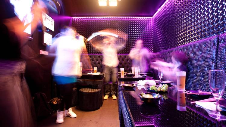 A shot of a group of people singing in a karaoke room at Mizuya