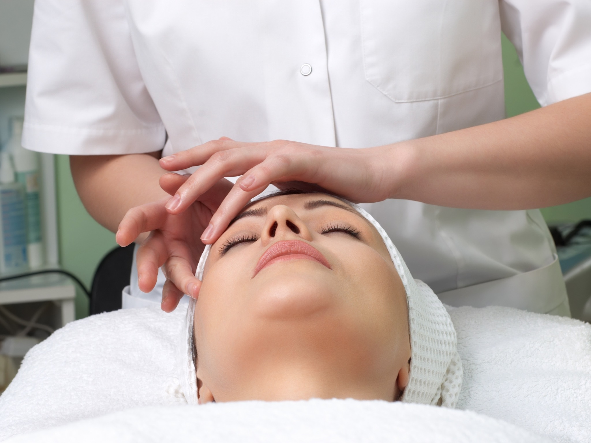 A generic shot of a woman at a spa receiving a head massage