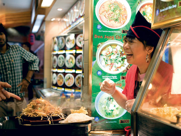 Woman serves up a Chinese dish to a customer