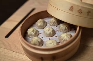 A close up shot of 8 dumplings in a bamboo steamer at Din Tai Fu