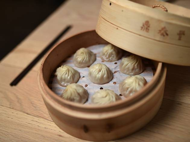 A close up shot of 8 dumplings in a bamboo steamer at Din Tai Fu