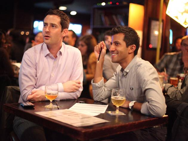 Men awaiting answers during a game of trivia