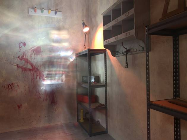 An escape room with shelving units, a lamp and blood smears on t