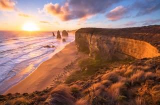 A landscape shot of a sunset going down next to the 12 Apostles