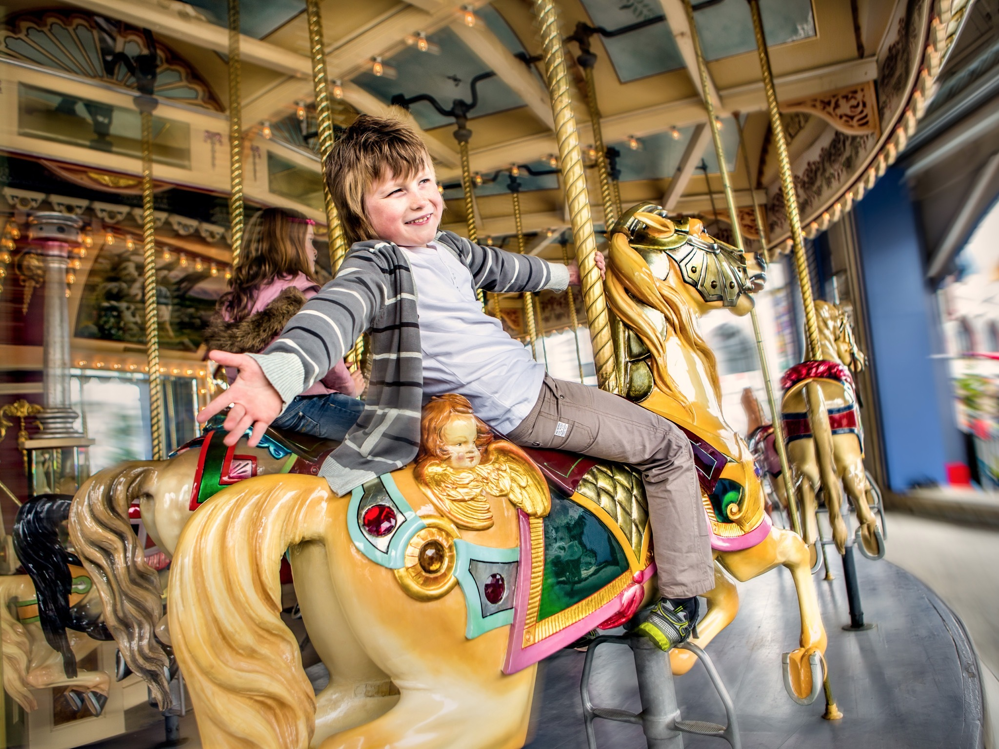 A boy rides a horse on the carousel at Luna Park