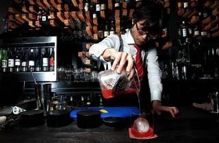 A shot of a bartender behind the bar at Hihou pouring a cocktail